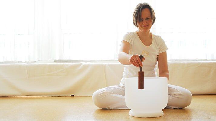 Klangmassage Lehrerin Christina Plate (ABATON Vibra) beim Anreiben einer großen Kristallklangschale